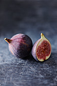 A whole and a half fresh fig on a gray background