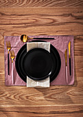Elegant place setting with black plates and gold cutlery