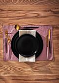 Elegantes Gedeck mit schwarzen Tellern und Goldbesteck