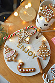 Decorated gingerbreads on a marble tray and christmas lollipop
