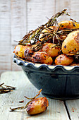 Roasted potatoes with sprigs of rosemary in a ceramic bowl