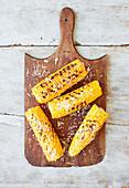 Gegrillte Maiskolben mit geriebenem Käse