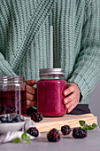 Person holding glass jug of delicious berry smoothie