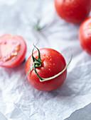 Frische Tomaten, ganz und halbiert auf Papier