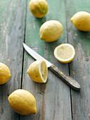 Zitronen, ganz und halbiert mit Messer auf Holzuntergrund