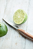 Halved lime with a kitchen knife on a light background