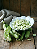 Broad beans in pods and in a bowl