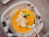 Orange Salmorejo cold soup decorated with slices of jamon and salted cracker