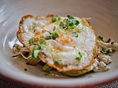Fried egg on tasty risotto with artichokes served with green sprouts on white plate