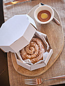 Ensaimada topped with powdered sugar in paper box on wooden table served with brown sauce