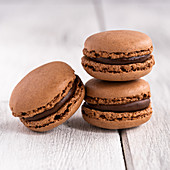 Macaroons stacked in pile against wooden white surface