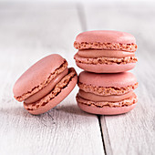 Pink macaroons stacked in pile against wooden white surface