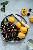 Frische Kirschen und Aprikosen auf Teller mit Messer