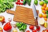 Frisches Gemüse, Blattsalat und Obst um ein Holzschneidebrett mit Messer