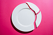 Broken white plate on pink background