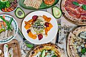 Buffet mit verschiedenen Pizzen, Bohnensalat mit Gemüsechips und Guacamole