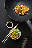 Fried chicken with Japanese traditional dish Oyakodon, with rice, fresh herbs, soy sauce and chopsticks