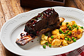 Roasted steak on bone with berry sauce and baked potatoes with young green peas on white plate