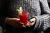 Woman in holding glass with red punch decorated with rosemary and slices of ginger