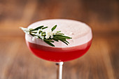 Glass with red cocktail consist of gin egg whites lime juice and raspberry syrup decorated with rosemary