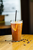 Cold coffee with ice and slices of lemon in glass with tube on wooden table with coffee bean