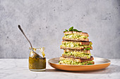Rye bread sandwiches with avocado puree with glass jar of pesto sauce