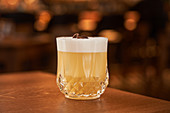 Glass of classic Whiskey Sour with lemon juice and egg white placed on wooden counter