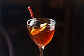 Red cocktail Manhattan garnished with cherry and orange zest on stick against dark background