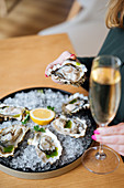 Person with glasses of champagne trying oysters with lemon and herbs