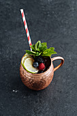 Metal mug with fruit drink with lime and berries decorated with mint leaves