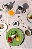 Reste eines Frühstücks mit Ei, Obst, Avocado, Croissants, Brot, Orangensaft und Schwarztee