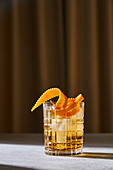 Glass cup with cold old fashioned cocktail with whiskey and orange peel