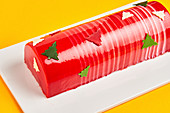 Cake with red icing and Christmas trees placed on board on yellow background