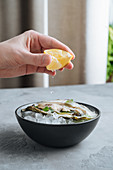 Person squeezing lemon on delicious oysters on Ice cuber on a bowl