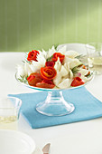 A glass cake stand with a bouquet of vegetable flowers