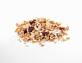 A pile of muesli with dried fruit and nuts on a white background