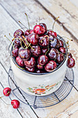 Fresh cherries in enamel bucket with water droops