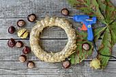 Zutaten für Kastanienkranz: Strohrömer, Kastanien und Heißklebepistole