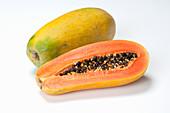 Papaya, whole and halved on a white background