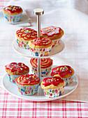 Muffins mit roter Glasur und Zuckerkonfetti auf Etagere