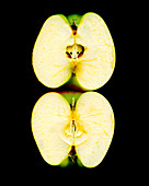 Two apple halves against a black background