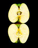 Zwei Apfelhälften vor schwarzem Hintergrund