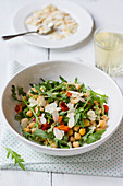 Salad made of rocket, roasted pepper, chickpeas and almonds, almond flakes, white wine