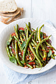 Fasolakia lathera - greek dish, green beans in tomato sauce with red onions and basil, bread