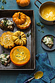 Pumpkin soup with rosmary and yogurt in small pumpkins, toasts with pears, kale and gorgonzola