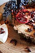 Halbierter Granatapfel, gebrannte Mandeln und Käse auf Holzscheibe
