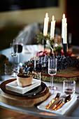 Festliches Gedeck auf Weihnachtstisch mit vier Kerzen
