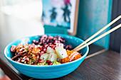 Poké bowl with salmon, mashed sweet potatoes and pomegranate seeds