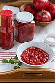 Homemade tomato puree in a ball and in jars, fresh tomatoes