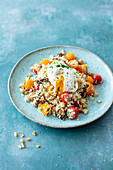 Couscous salad with tomatoes, chickpeas and poached egg